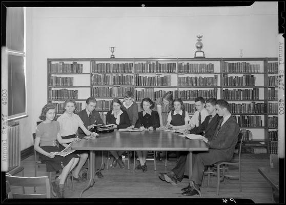 Versailles High School, Annual Staff; members sitting around a table in the library