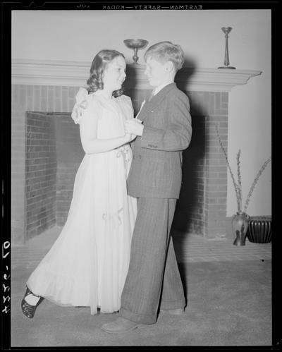 Margorie Hall; dance, a girl and a boy dancing in front of a fireplace