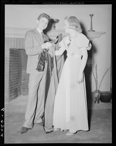 Margorie Hall; dance, a boy helping a girl with her coat in front of a fireplace