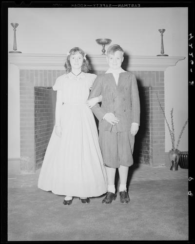 Margorie Hall; dance, a girl and a boy posing for their portrait in front of a fireplace