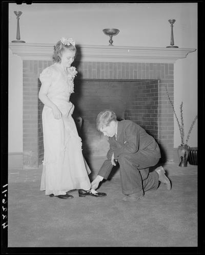 Margorie Hall; dance, a boy helping a girl with her shoe in front of a fireplace