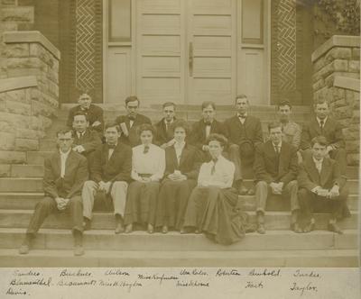 Fifteen people, twelve men, three women, names listed below picture