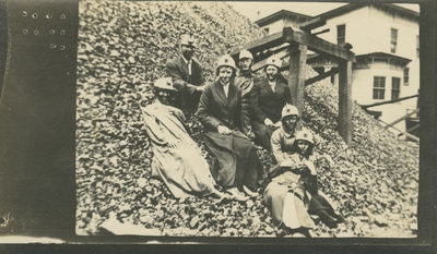 7 men and women at a coal camp sitting on the side of a large mound