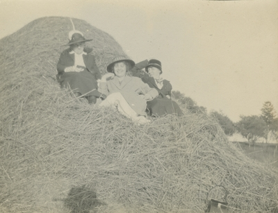 3 women sitting in a hay stack