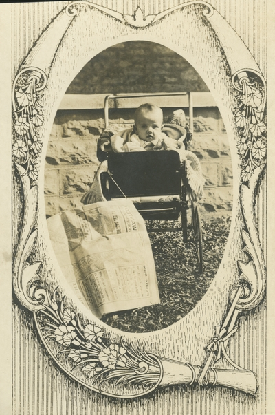 postcard with a decorative border, a baby sitting in a baby carriage