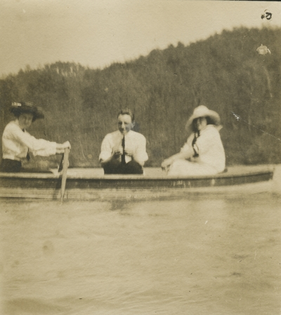 2 women and a man sitting in a boat out in the water