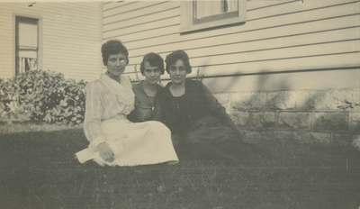 3 women sitting on the grass with houses in the background