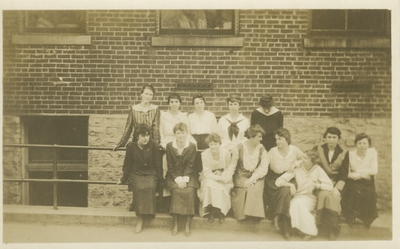 a group of women standing against a building