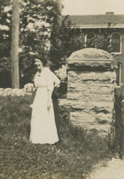 a woman standing outside next to a stone wall