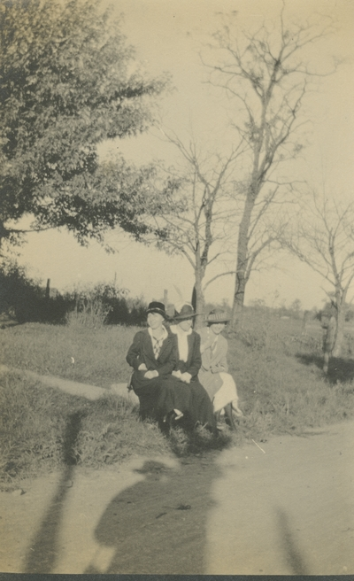 3 women sitting on the grass next to the road