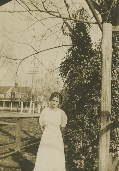 a woman standing by fence with a house in the background
