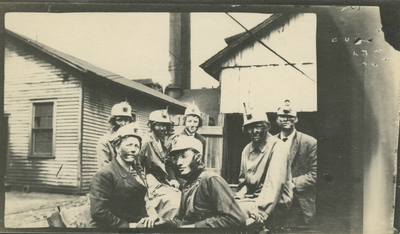 7 men and women (appear to be the same people as item #6 and #7) at a coal camp with buildings in the background