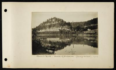 Multiple long low buildings on far bank, two large buildings with chimneys, two boats in foreground on near bank, notation                          Boone's Knob mouth of Hickman (Camp Nelson) 1907