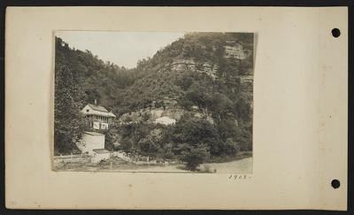 House at base of bluffs, three other buildings around it, stone and wooden fences, bluffs rising on right, mouth of cave barely visible