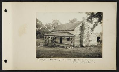 House with stone chimney, one man standing on nearest edge of porch, one man leaning back in his chair and two women sitting at opposite end of porch, wooden fence extending from porch to small building behind house, notation                          Perryville Battlefield 1907 Bottom's House, below the stone fence