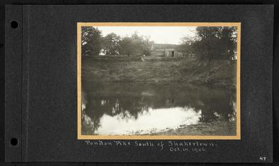 Dilapidated wooden building with fallen wooden fencing in front on bank of small pond, notation                          Pondon Pike South of Shakertown Oct. 14. 1906