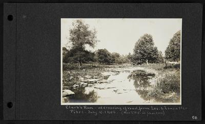 Shallow river with small rocks, woman and horse drawing phaeton in background, notation                          Clark's Run - at crossing of road from Lex. To Lancaster Pikes - July 4, 1906. Mrs. T.P.C. in Phaeton