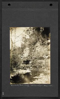 Creek with bluffs rising up the right hand bank, man standing on rocks on edge of creek with camera on tripod, notation                          Harrod's Run Cliff, H.G. Candifer, May 2, 1907