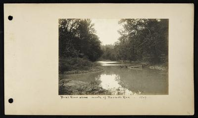 Calm section of river, large flat rock in water with fallen branches, fallen tree in background, notation                          Dick's River above mouth of Harrod's Run 1907