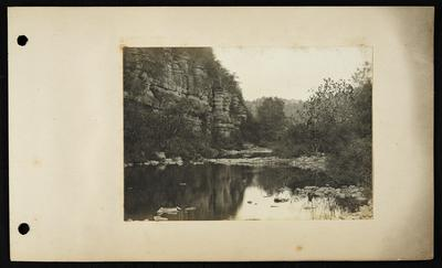 Calm river with flat rocks on right bank extending almost to left bank, bluffs on left, buildings on hilltop in distance