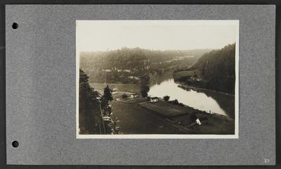 River running into a fork, timber along banks, collection of buildings on far right bank, houses on left bank, small structure on top of bluff with steep stairs