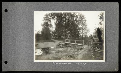 Small bridge over dried up river, railing on one side, fencing in right foreground, road leading away from bridge on left, notation                          Germantown Bridge