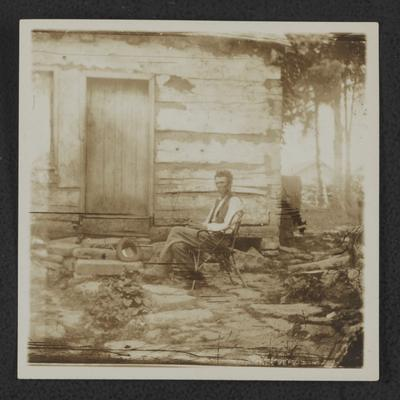Man sitting in front of log house