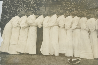 Group portrait of women, leaning on each other in a row (a back view)