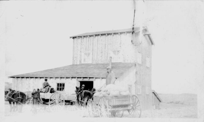 Two horse drawn wagons with Native American men in the wagons and a Native American Woman holding a child standing beside the wagons.  Handwritten note on back of photo