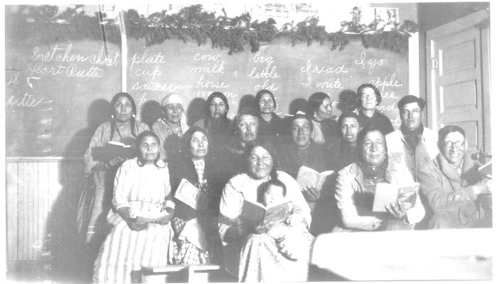 A group of Native Americans and sitting in front of a chalk board.  A typed sheet of paper is attached identifying the group
