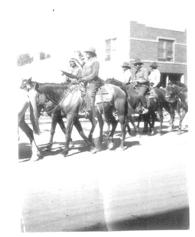 Native Americans riding horses through the streets of a town