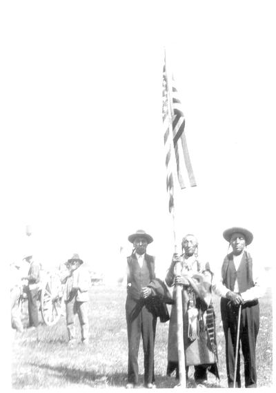 Three Native American men standing around an flag pole flying around the US Flag