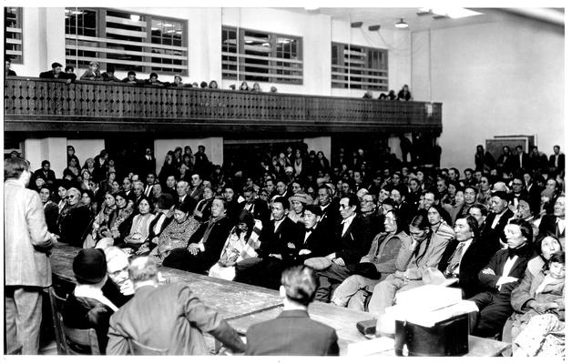 A large group of Native Americans sitting in an audience.  Children are sitting in the balcony area.  A typed label identifies group as