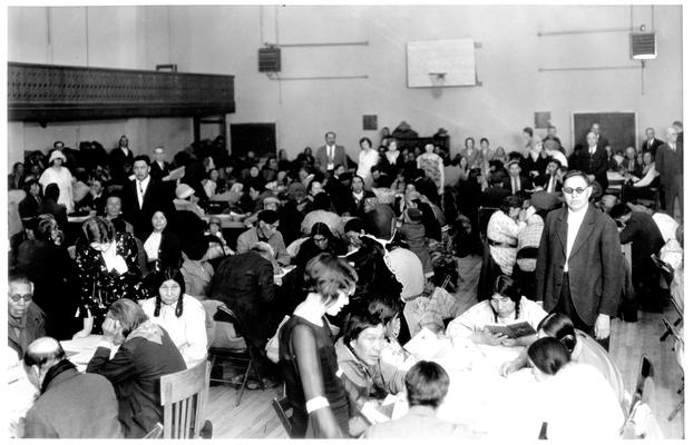 Small groups of Native Americans sitting at tables learning to read.  In a gymnasium on the Blackfeet Reservation