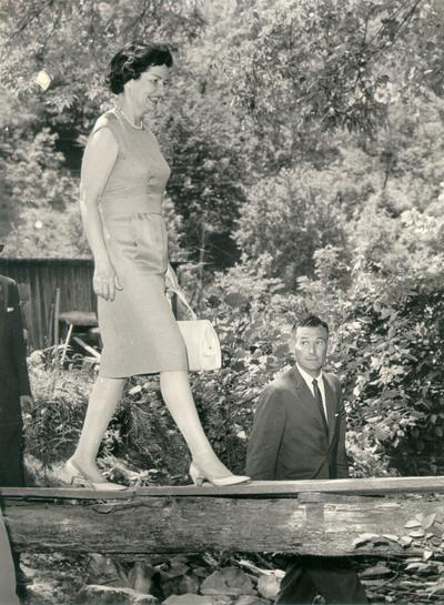 Johnson, Lyndon B. and Ladybird; The First Lady walking across a wooden plank