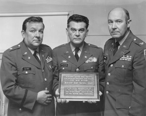Kentucky Easter Seal Society; Three members of the Kentucky Army National Guard pose with a plaque in their honor