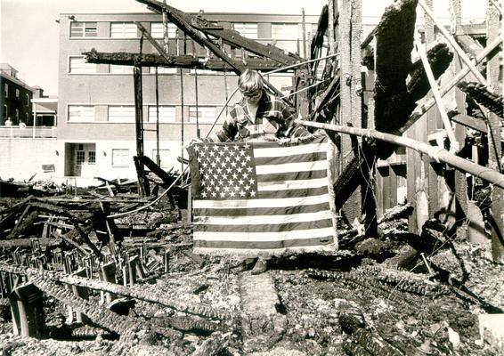 Ashland Bulk Oil Plant; 1973 Explosion and Fire; A man holds a frayed American Flag; burned building in the background