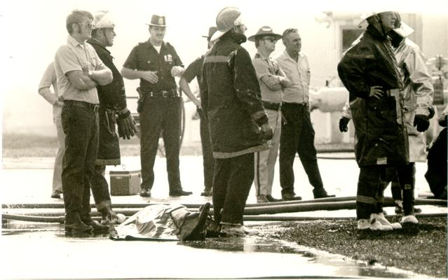 Ashland Bulk Oil Plant; 1973 Explosion and Fire; Firemen and authorities stand near body of one of the dead