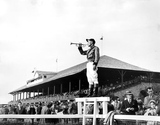 Horses; Thoroughbred Racing; Keeneland; Scenes at the Track; Man blowing trumpet in front of the grand stand