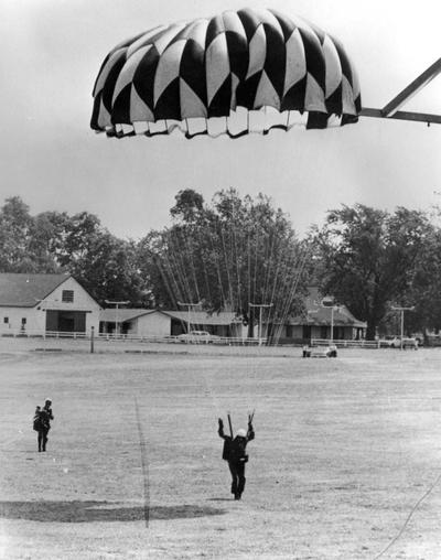 Planes, Helicopters, and Parachutists; A parachutist touches down
