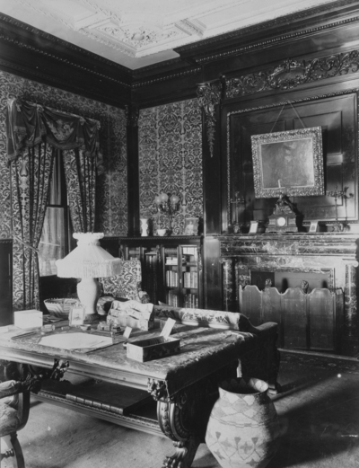 Library, Interior of Elmendorf Mansion, a desk is in the center of the room, bookshelves and a fireplace line the wall. Silver Print