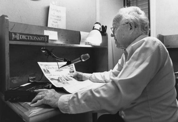 Crabb, Alfred L., Jr., Professor, English Education Department, pictured reading newspaper over the radio for a program intended for blind listeners,
