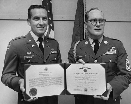 Digman, Robert D., Professor, ROTC Program, Master Sergeant, United States Army, pictured receiving the Army's Meritorious Service Award on the occasion of his retirement after more than 20 years of service, Major James G. Coston (left) presents the award