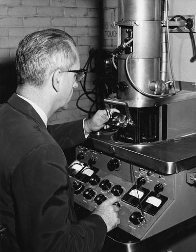 Edwards, Ogden Frazelle, Professor of Bacteriology, Biological Sciences Department?, pictured with electron microscope