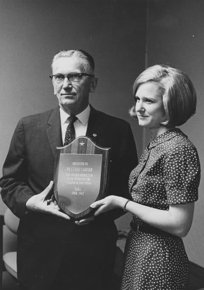 Ginger, Lyman Vernon, Dean, College of Education, 1956 - 1967, Superintendent of Instruction for Kentucky, President of Kentucky Education Association, President and Treasurer of National Education Association, Alumnus, Master of Arts, 1942, Ed.D., 1950, pictured receiving a plaque from Karen Kiel, president of Kentucky Student Education Association