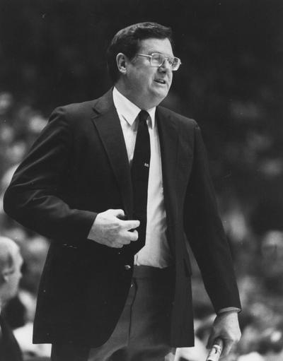Hall, Joe B., University of Kentucky Men's Basketball Coach 1972-1985 in a familiar sideline stance program in hand, Athletic Department