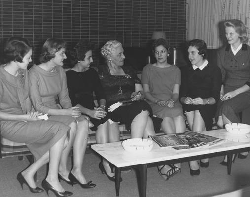 Holmes, Sarah Bennett, born 1886, University of Kentucky Dean of Women 1944-1957,  She disscuses various phases of dormitory life at Holmes Hall with several residents, Left to Right are:  Mary Otis Howell, Hodgenville; George Ann McGinley, Bowling Green; Mrs. Holmes; Sylvia Norris, Pikeville; Sue Harrollson, Owensboro