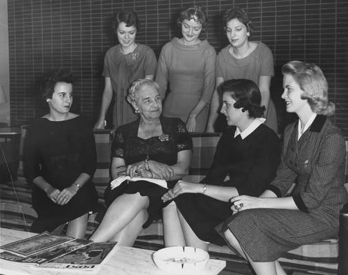 Holmes, Sarah Bennett, born 1886, University of Kentucky Dean of Women 1944-1957,  She discusses various phases of dormitory life at Holmes Hall with several residents, Left to Right are:  Mary Otis Howell, Hodgenville; George Ann McGinley, Bowling Green; Mrs. Holmes; Sylvia Norris, Pikeville; Sue Harrollson, Owensboro