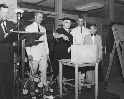 Holmes, Sarah Bennett, born 1886, University of Kentucky Dean of Women 1944-1957,  Holmes Hall Cornerstone Prepared:  Three graduates of Mrs. Sarah Bennet Holmes place a box of memorabilia into the conerstone of Holmes Hall at dedication exercises, From left are University of Kentucky President Dickey, and her grandsons Robert Broadbent, Cadiz; Mrs. Holmes; Smith Broadbent, Cadiz and John Holmes Jr., Louisville
