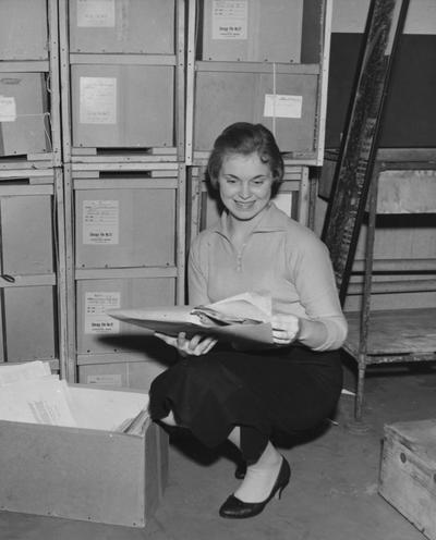 Hughes, Delmar, a member of the University of Kentucky library staff, going through some of the papers that were included in the Barkley collection now on deposit at the University of Kentucky's Margaret I. King Library, From Public Relations Department